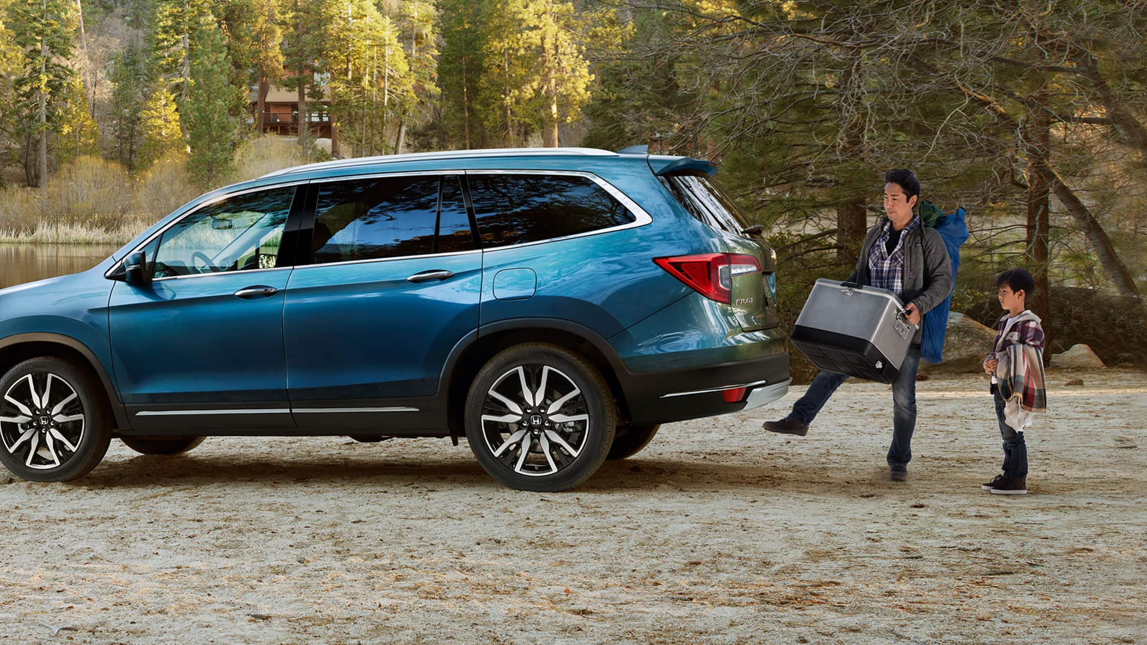 Driver's side profile view of 2020 Honda Pilot Elite in Steel Sapphire Metallic parked next to a lake displaying the hands-free access power tailgate.
